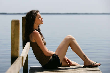 Woman sat on the end of wooden jetty photo