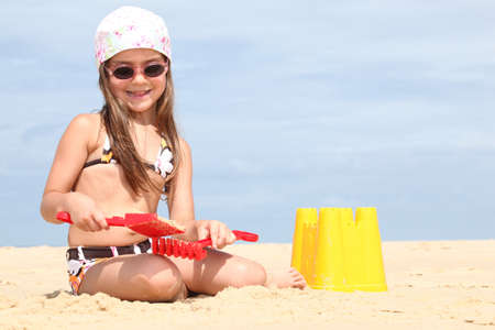 sandcastles: Young girl making sandcastles on a beach Stock Photo