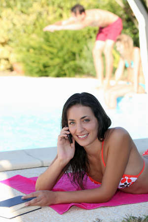 Woman lounging by the pool photo