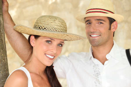 all smiles: couple all smiles wearing straw hat Stock Photo