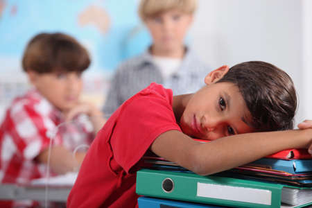 Little boy resting in class. photo