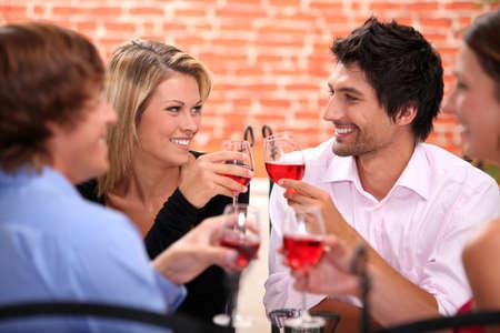 pareja comiendo: Cuatro amigos bebiendo en el restaurante