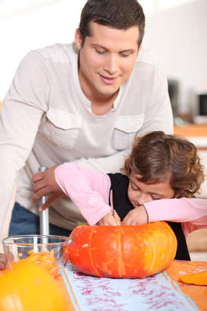 4 7: Dad and his daughter carving pumpkins in the kitchen Stock Photo