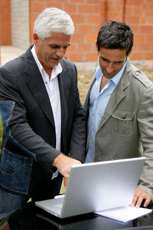 Men on a building site with a laptop Stock Photo - 12218073