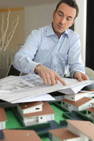implications: An architect pointing to a blueprint