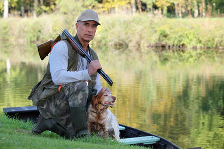 kneeled: A hunter and his dog by a river.