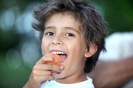 hungry kid: Boy eating an apricot Stock Photo