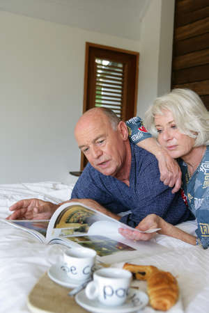 Senior couple looking at a magazine in bed photo