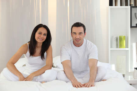 couple sitting in their bed photo