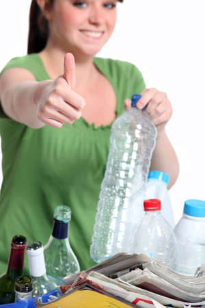 separate: Young woman recycling plastic bottles