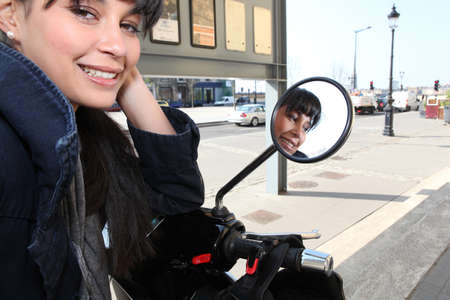 Young woman on a moped in  town photo