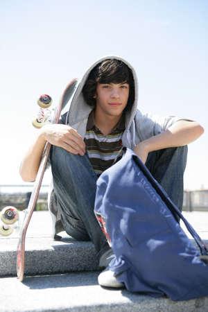 niño en patines: Boy sentado en un escalón con skate
