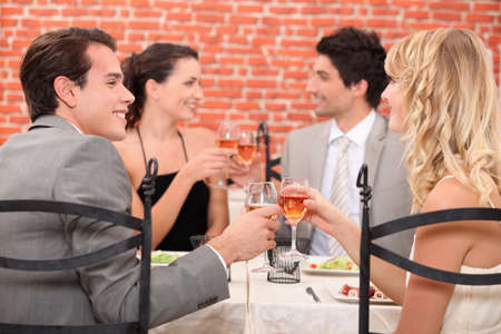 dinner wear: Friends raising their glasses in a toast at a restaurant