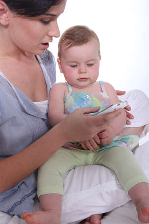 Mother resting baby on knee whilst looking at mobile telephone photo