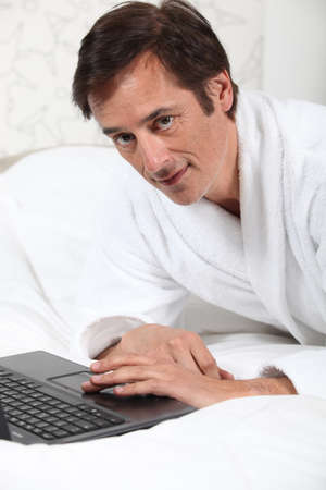 45 55 years: Man working in dressing gown. Stock Photo