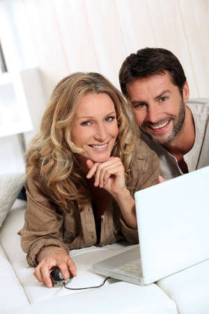 35 40 years: Couple smiling on laptop.