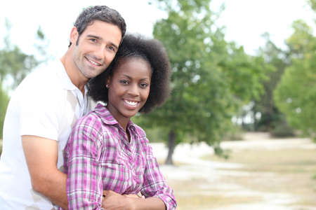 Mixed race couple hugging in the countryside photo