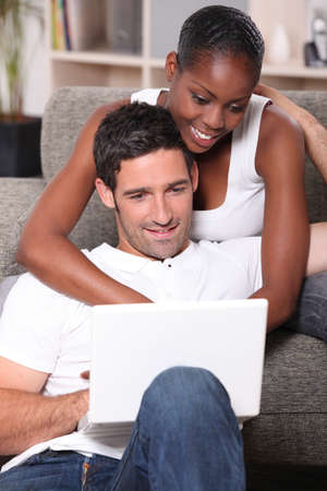 black woman is cuddling her boyfriend and doing computer photo