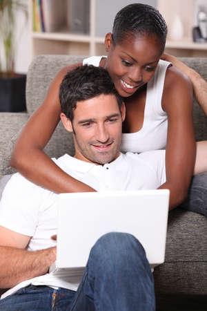 interracial: schwarze Frau ist ihrem Freund kuscheln und dabei Computer