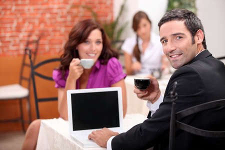 Man using a laptop computer in a cafe with a blank screen for your image photo