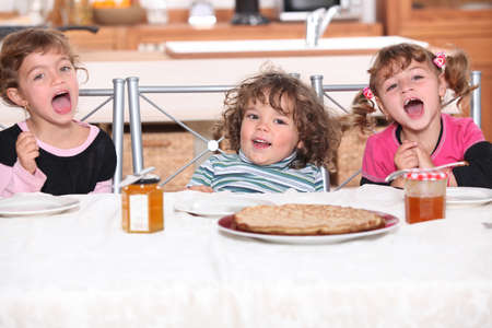 brothers and sisters: children eating a pie Stock Photo
