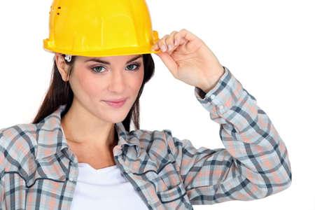 safety vest: Female builder touching hat