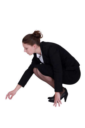 dark haired woman: Businesswoman picking a speck up off the floor
