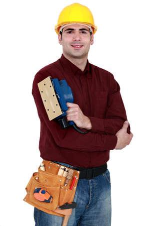 sander: Tradesman holding a sander