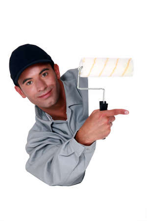 Tradesman holding a paint roller and pointing to a blank sign Stock Photo - 12217850