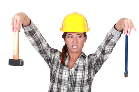 workwoman: Revolted woman looking at her tools Stock Photo