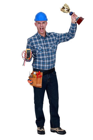 voltmeter: Man with a voltmeter and a trophy in hand Stock Photo