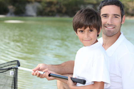 Father and son fishing on boat photo