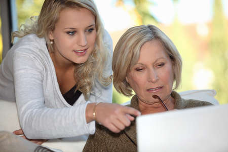 Granddaughter showing her grandmother how to use a computer photo