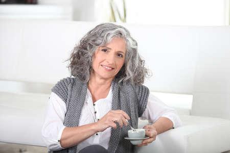 Vrouw, zittend op de vloer met een kopje koffie