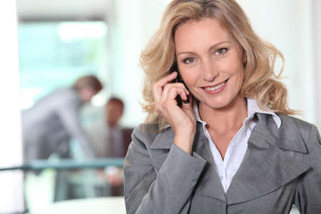 Businesswoman using a cellphone in an office Stock Photo - 12218773