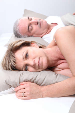 nap: Mature couple laid in bed Stock Photo