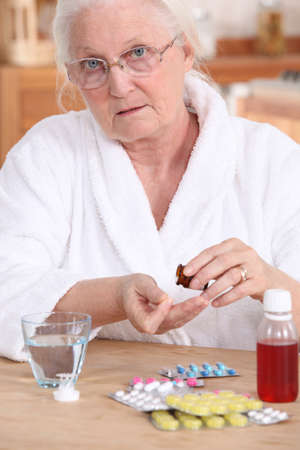 Older woman taking medicine photo