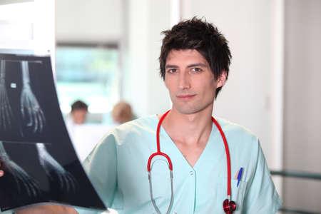 trained nurse: Male nurse examining x-ray image