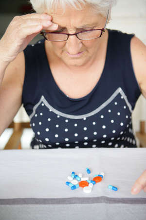 resent: An elderly woman looking at her medication Stock Photo