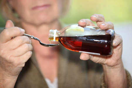 cough medicine: Woman taking cough medicine