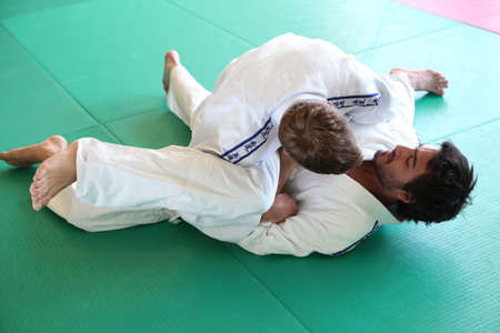 Judo practitioners in a hold on mat photo