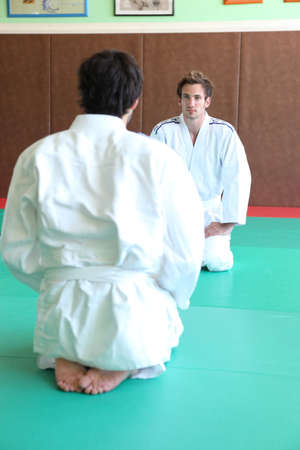 Men at the start of a judo match photo