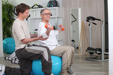 Older woman working out with a personal trainer at the gym photo