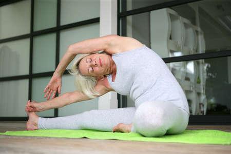 welfare: Senior lady doing yoga stretching Stock Photo