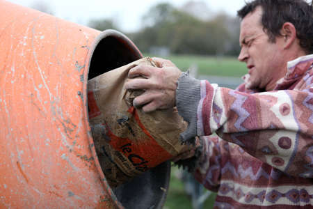mucky: Man putting cement in a mixer