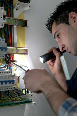 Man repairing electrical panel photo