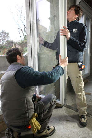 Two workers fitting window Stock Photo - 12219342