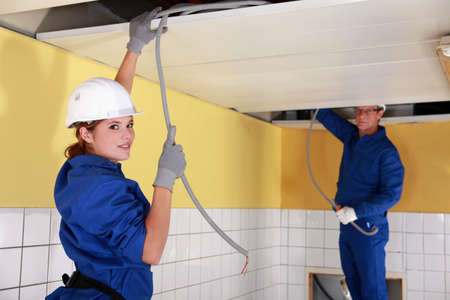 cabling: Young female electrician with mentor Stock Photo