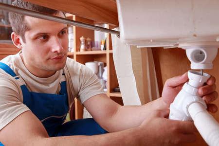 securing: Plumber fixing sink