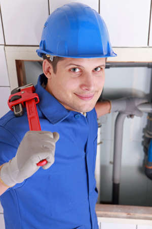 Plumber installing pipes with a large wrench photo